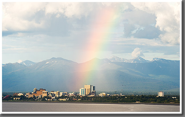 A passing thunderstorm creates a bright rainbow over downtown Anchorage, Alaska.