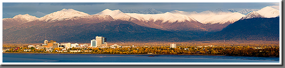 The warm glow of the setting sum illuminates the freshly snow-covered peaks of the Chugach Mountains while Anchorage is surrounded by the golden colors of Fall.